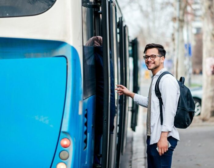 Handsome smiling young man getting into bus.